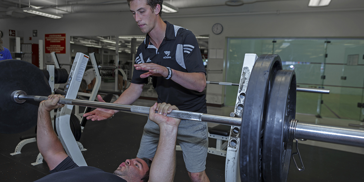 A Gee-Gees personal trainer helps a client