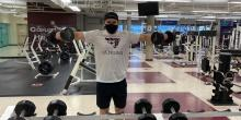 Man lifting weights while wearing a mask