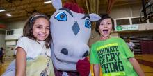 Girl beside the mascot and boy with a green shirt.