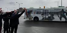Crowed waving at the Ottawa 2021 bus.