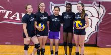 Photo of 5 girls, two holding volleyballs, in front of uOttawa Gee-Gees branded wall.