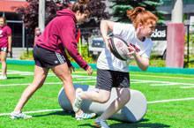 Joueuse de rugby lors du camp, portant le ballon.
