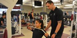 Girl training and personal trainer helping her.
