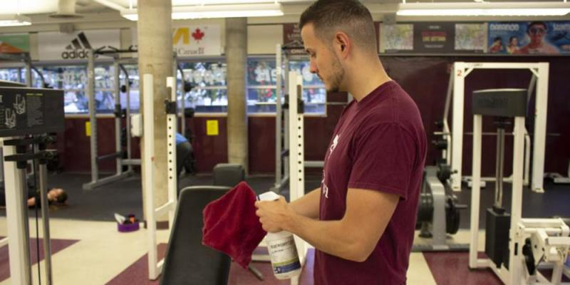 A fitness centre patron wipes a machine after using it