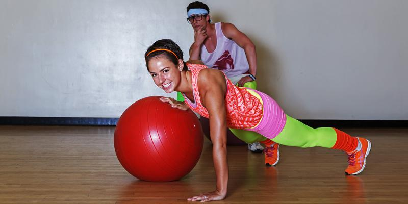 People in fluo: girl on a big training ball and men thinking behind.