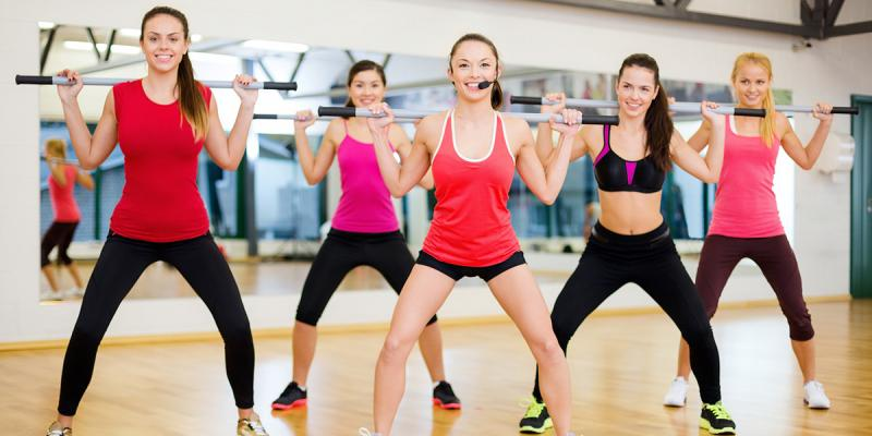 Group of women doing fitness with a bar behind their back.
