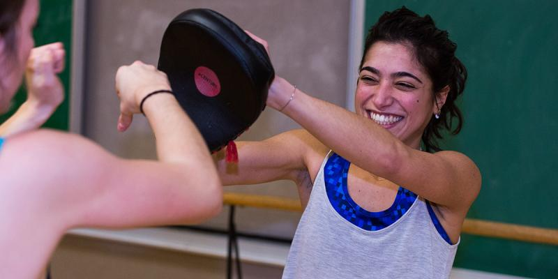 Girls holding a kickboxing mit, and laughing.