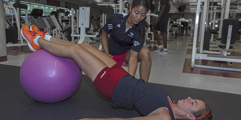 Personal trainer helping a women.