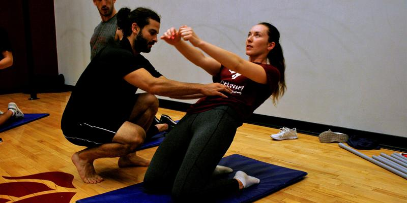 Girl stretching with a trainer.