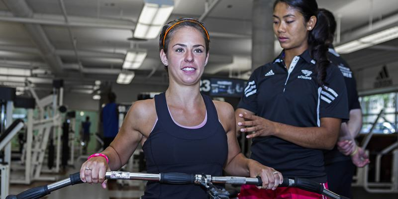 Girl pulling a bar with a personal trainer helping her.